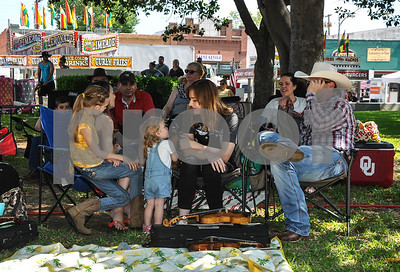 A family relaxes under a tree while attending the 87th Annual Old Fiddlers Contest & Reunion in Athens. People came from all over the state to compete in the contest, which included 6 divisions, on Saturday, May 26. (Jessica T. Payne/Tyler Paper)