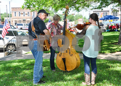Musicians rehearse in the shade before taking the stage at the 87th Annual Athens Old Fiddlers Contest & Reunion. The Fiddlers Contest was held at the Athens Courthouse square on Saturday, May 26. (Jessica T. Payne/Tyler Paper)