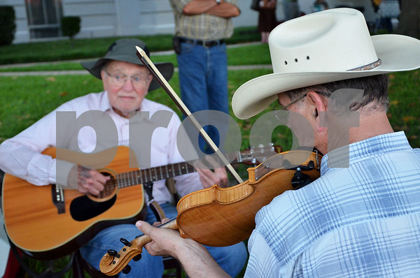 Dick Moorehead plays the fiddle while Gene Gimble plays guitar in a jam session circle outside the Henderson County Courthouse in Athens. (Victor Texcucano)