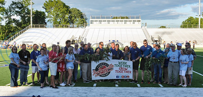 Members of the Jacksonville ISD school board, Jacksonville Chamber of Commerce and the City of Jacksonville gather on the field to cut a tomato vine as part of the Ribbon Cutting and Grand Re-Opening of the historic Tomato Bowl on Friday, June 7. A special free admission concert by country music singer and Jacksonville native Neal McCoy also took place. (Jessica T. Payne/Tyler Morning Telegraph)