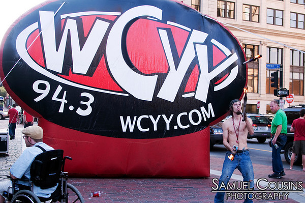 Fire juggler in front of the WCYY sign, at the Alive at Five concert series in Monument Square.