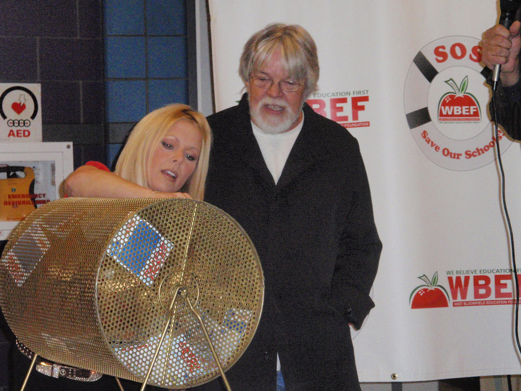 . Karen Newman and Bob Seger pick the winner  at Save Our Schools raffle for West Bloomfield schools.