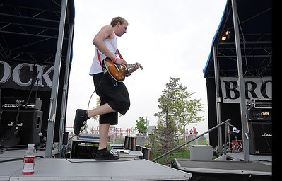 Taylor Kaufman guitarist for 'No Less Than Victory' walks between  stages  while playing during Broomstock at the Broomfield County Commons Park on Thursday. May 26, 2011 staff photo/David R. Jennings