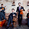 "Brooklyn Rider <br /> Photo by Sarah Small<br /> The adventurous, genre-defying string quartet Brooklyn Rider combines a wildly eclectic repertoire with a gripping performance style that is attracting legions of fans and drawing critical acclaim from classical, world and rock critics. NPR credits Brooklyn Rider with ""recreating the 300-year-old form of string quartet as a vital and creative 21st-century ensemble."" The musicians play in venues as varied as Joe's Pub and Alice Tully Hall in New York City, Todai-ji Temple in Japan, Library of Congress, San Francisco Jazz and the South By Southwest Festival. Through creative programming and global collaborations, Brooklyn Rider illuminates music for its audiences in ways that are ""stunningly imaginative"" (Lucid Culture).<br /> <br /> During the past year, Brooklyn Rider recently released the albums Brooklyn Rider Plays Philip Glass, which was selected as one of NPR Classical's Best Albums of the Year (So Far), and Seven Steps, featuring their interpretation of Beethoven's String Quartet in C-sharp minor.<br /> <br /> In recent seasons, Brooklyn Rider has appeared at Lincoln Center's Tully Scope Festival, the Cologne Philharmonie, American Academy in Rome, Malmö Festival in Sweden, Spoleto Festival USA, the Kimmel Center in Philadelphia and SXSW Festival as the only classical group invited to play there. The Los Angeles Times reviewed one of the concerts from an extensive cross-country tour, saying, ""The dazzling fingers-in-every-pie versatility that Brooklyn Rider exhibits is one of the wonders of contemporary music.""<br /> <br /> Born out of a desire to use the rich medium of the string quartet as a vehicle for communication across a large cross section of history and geography, Brooklyn Rider is equally devoted to the interpretation of existing quartet literature and to the creation of new works. The musicians have worked with such composers as Derek Bermel, Lisa Bielawa, Ljova, Philip Glass, Osvaldo Golijov, Jenny Scheinman and Dmitri Yanov-Yanovsky, and they also regularly perform pieces written or arranged by members of the group. Another integral part of their work involves creative collaborations with other artists. A long-standing relationship between Brooklyn Rider and Kayhan Kalhor resulted in the critically acclaimed 2008 recording, Silent City, selected by Rhapsody.com as one of World Music's Best Albums of the Decade.<br /> <br /> Brooklyn Rider often appears under the umbrella of outside initiatives begun by all four members of the group. In 2003 violinist Johnny Gandelsman created In A Circle, a series of performance events in Lower Manhattan and Brooklyn that explore connections between music and the visual arts. He launched In A Circle Records in 2008 with the release of Brooklyn Rider's eclectic debut recording, Passport, followed by Dominant Curve in 2010. Both albums made NPR's year end round-ups: Best Classical CDs of 2008 and 50 Favorite Albums of 2010. The recordings have received glowing reviews from Gramophone, Strings, The Strad and Huffington Post, as well as the online indie magazines Pitchfork, Vice, Nerve and Lucid Culture. ""Forgive the hyperbole,"" wrote Strings, ""but I've seen the future of chamber music and it is Brooklyn Rider.""<br /> <br /> Brothers Colin and Eric Jacobsen are co-founders of The Knights, a New York-based orchestra in which all the members of Brooklyn Rider play. The quartet also founded the Stillwater Music Festival (MN) in 2006 as a place to unveil new repertoire and collaborations. As educators, Brooklyn Rider has enjoyed residencies at Williams College, MacPhail Center for the Arts, Dartmouth College, Texas A&M University, Denison University and University of North Carolina, as well as Sewanee Summer Music Festival and Laguna Beach Chamber Music Festival.<br /> <br /> Much of Brooklyn Rider's desire to extend the borders of conventional string quartet programming has come from their longstanding participation in Yo-Yo Ma's Silk Road Ensemble. As individual members of the ensemble, they have performed throughout the world, recorded three albums for Sony Classical, and taken part in educational initiatives, family concerts and media broadcasts. Members of Brooklyn Rider have been involved in a series of museum residencies initiated by the Silk Road Project at the Rubin Museum of Himalayan Art and the American Museum of Natural History in New York City, the Art Institute of Chicago, the Museum Reitberg in Zurich and the Nara National Museum in Japan. They have also participated extensively in Silk Road Ensemble residencies at Harvard University and the Rhode Island School of Design.<br /> <br /> A public radio favorite, Brooklyn Rider has been featured on NPR's Tiny Desk Concerts, All Songs Considered, Deceptive Cadence and All Things Considered, WNYC's Soundcheck and American Public Media's Performance Today, as well as NY1 News TV in New York City. Their recordings are played across North America on stations ranging in focus from classical to world, jazz, pop and new music.<br /> <br /> The quartet's name is inspired in part by the cross disciplinary vision of Der Blaue Reiter (The Blue Rider), a pre-World War I Munich-based artistic collective whose members included Vassily Kandinsky, Franz Marc, Arnold Schoenberg and Alexander Scriabin. In this spirit, Brooklyn Rider has created an online art gallery that showcases the work of some of their friends. Proceeds are used to support new commissioning projects. In the eclectic spirit of Der Blau Reiter, the group also draws inspiration from the exploding array of cultures and artistic energy found in the borough of Brooklyn in New York City, a place they call home."