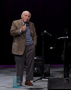 "George Wein giving his acceptance speech with the Clearwater ""Power of Song"" award by his feet."