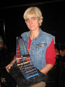 Terry Dame: composer, instrument builder, multi-instrumentalist, and high energy performer.  The elastic bands on this instrument made of coathangers are amplified and played with thin sticks, producing surprisingly low, loud sounds.