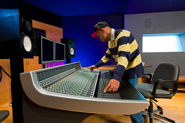 Recording engineer or music producer mixing music on a mixing console in a recording studio