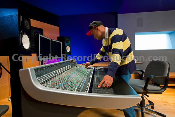 This photo has model release and is available for commercial use. Recording engineer or music producer mixing music on a mixing console in a recording studio