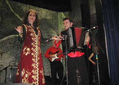 Merita Halili holds her microphone over towards her husband's accordion. Raif Hyseni is a master accordionist. Note the black cloth covering his keyboard.  He plays through the cloth.