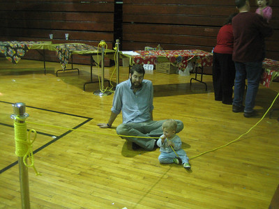 Tables are being set up for snacks, while a very young guest plays with a rope.  Future string player?