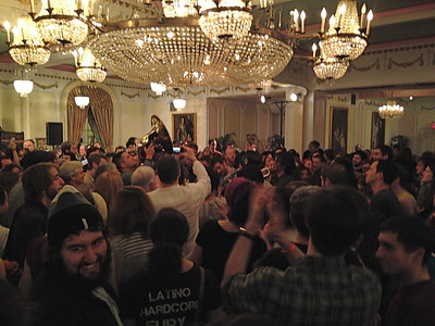 "Downstairs in the Chopin Room, a crowd surrounds The Raya Brass Band, which plays ""exuberant, original brass band music."""