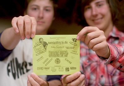 Jake (left) and Zach Schweitzer hold a flyer from the Smoking Popes' first show.