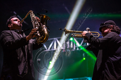 LOS ANGELES, CA - AUGUST 25:  Saxophonist Ulises Bella (L) and vocalist Asdrubal Sierra of Ozomatli perform at Univision Radio's H2O music festival at Los Angeles Historical Park on August 25, 2012 in Los Angeles, California.  (Photo by Chelsea Lauren/WireImage)