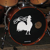 The Textbook Committee drumhead with a rooster with sixpack rings round' his neck.