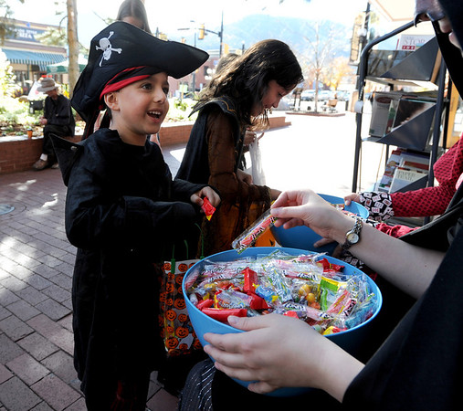 """Arvin Rezvani, 5,, left, gets candy from Stephanie Schindheln of the Boulder Book Store.<br /> Over 80 downtown businesses provided treats to kids of all ages at the annual Munchkin Masquerade.<br /> For more photos and a video of the Munchkin Masquerade, go to  <a href=""""http://www.dailycamera.com"""">http://www.dailycamera.com</a>.<br /> Cliff Grassmick  / October 31, 2012"""