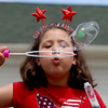 "Brianna LePlatt, 9, blows bubbles to the crowd from one of the holiday floats.<br /> The Niwot Rotary Club and the Niwot Business Association hosted the Niwot Fourth of July festival and parade on Sunday.<br /> For more photos of the parade, go to  <a href=""http://www.dailycamera.com"">http://www.dailycamera.com</a>.<br />  Cliff Grassmick / July 4, 2010"