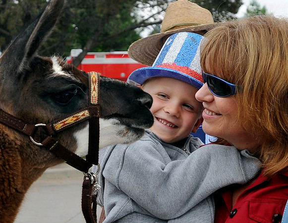 "Zack Turpin, and his aunt, Judy Labuda, get a kiss from a llama before the parade.<br /> The Niwot Rotary Club and the Niwot Business Association hosted the Niwot Fourth of July festival and parade on Sunday.<br /> For more photos of the parade, go to  <a href=""http://www.dailycamera.com"">http://www.dailycamera.com</a>.<br />  Cliff Grassmick / July 4, 2010"