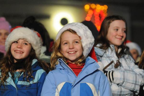 Chole Wilkins, 9 left, and Rhys Hayzlett, 9, smile as they listen to the Broomfield Council sing at the Holiday Tree Lighting Ceremony at the Broomfield City and County Building on Friday<br /> December 4, 2009<br /> Staff photo/David R. Jennings