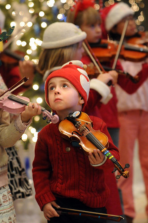 Casey Walker, 3, watches other Suzuki Violin Students play for the Holiday Tree Lighting Ceremony at the Broomfield City and County Building on Friday.<br /> December 4, 2009<br /> Staff photo/David R. Jennings