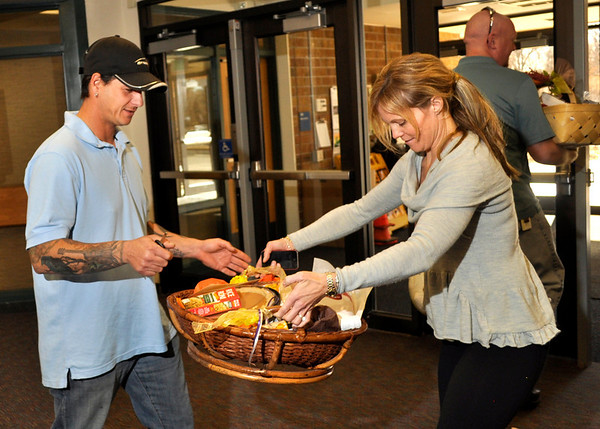 Curt Sarinopoulos, left, receives a Thanksgiving basket from Lori Vantassel at Ryan Elementary, where the Ryan Elementary community came together to make Thanksgiving baskets for families in need, in Lafayette on Monday Nov. 19, 2012. DAILY CAMERA/ JESSICA CUNEO.