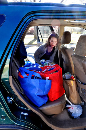 Melia Syed, first grade teacher at Ryan Elementary, loads up a car with Thanksgiving food that the Ryan Elementary community gathered for families in need, at Ryan Elementary in Lafayette on Monday Nov. 19, 2012. DAILY CAMERA/ JESSICA CUNEO.