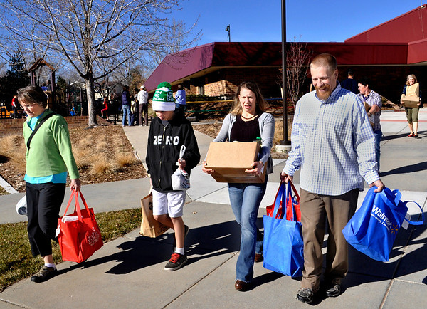 Kathy Butler, left, Konner Syed, Melia Syed, and Andy McCullough carry Thanksgiving food that the Ryan Elementary community gathered to make Thanksgiving baskets for families in need in Lafayette on Monday Nov. 19, 2012. DAILY CAMERA/ JESSICA CUNEO.
