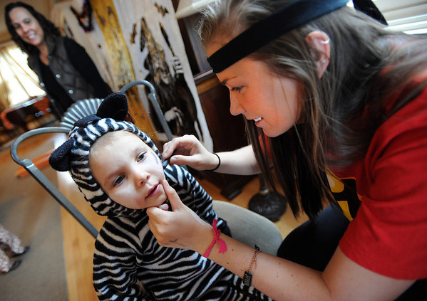 "Callie Marks, 4, get her face painted by Hanna Doyle of the Kappa Kappa Gamma house on Sunday.<br /> The Kappa Kappa Gamma Society at the University of Colorado held the 7th annual Halloween House to benefit BoulderReads.<br /> For more photos at Kappa Kappa Gamma, go to  <a href=""http://www.dailycamera.com"">http://www.dailycamera.com</a>.<br /> Cliff Grassmick / October 28, 2012"