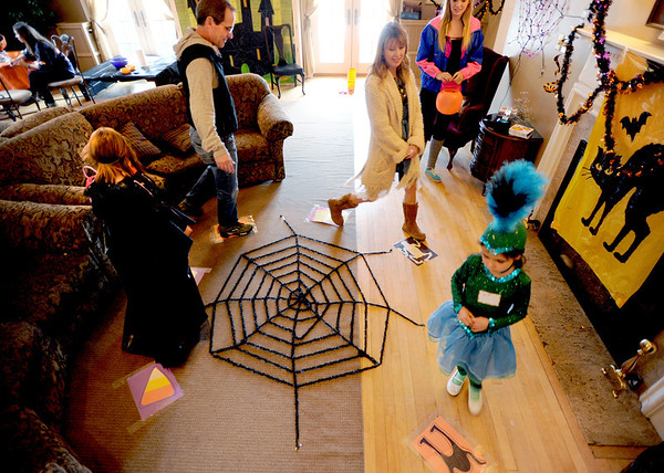 "Kylie Pazol, left, and sister, Rylan, play one of the games with their parents, Todd and Erika, at the Kappa Kappa Gamma house on Sunday.<br /> The Kappa Kappa Gamma Society at the University of Colorado held the 7th annual Halloween House to benefit BoulderReads.<br /> For more photos at Kappa Kappa Gamma, go to  <a href=""http://www.dailycamera.com"">http://www.dailycamera.com</a>.<br /> Cliff Grassmick / October 28, 2012"