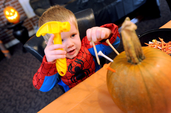 """Michael Fairchild, 2, hammers in some tees in a pumpkin at the Kappa Kappa Gamma house on Sunday.<br /> The Kappa Kappa Gamma Society at the University of Colorado held the 7th annual Halloween House to benefit BoulderReads.<br /> For more photos at Kappa Kappa Gamma, go to  <a href=""""http://www.dailycamera.com"""">http://www.dailycamera.com</a>.<br /> Cliff Grassmick / October 28, 2012"""