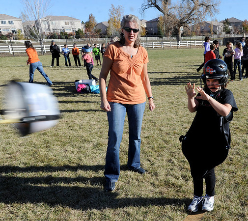 """Volunteer, Cheryl McMath, left, helps Maddie Hansen, a 4th-grader, launch her pumpkin.<br /> Students at Coyote Ridge Elementary School in Broomfield, combine science with Halloween with pumpkin launchings on Wednesday.<br /> For a video  and more photos of the pumpkin launch at Coyote Ridge Elementary, go to  <a href=""""http://www.broomfieldenterprise.com"""">http://www.broomfieldenterprise.com</a>.<br /> Cliff Grassmick  / October 31, 2012"""