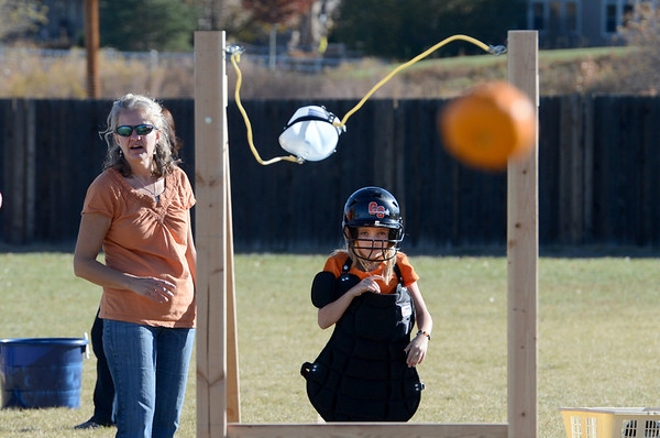 """Volunteer, Cheryl McMath, left, helps Emily Nenemaker, a 4th-grader, launch her pumpkin.<br /> Students at Coyote Ridge Elementary School in Broomfield, combine science with Halloween with pumpkin launchings on Wednesday.<br /> For a video  and more photos of the pumpkin launch at Coyote Ridge Elementary, go to  <a href=""""http://www.broomfieldenterprise.com"""">http://www.broomfieldenterprise.com</a>.<br /> Cliff Grassmick  / October 31, 2012"""