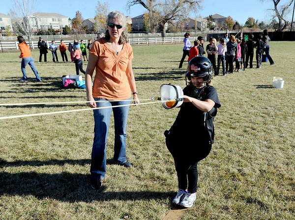"Volunteer, Cheryl McMath, left, helps Maddie Hansen, a 4th-grader, launch her pumpkin.<br /> Students at Coyote Ridge Elementary School in Broomfield, combine science with Halloween with pumpkin launchings on Wednesday.<br /> For a video and more photos of the pumpkin launch at Coyote Ridge Elementary, go to  <a href=""http://www.broomfieldenterprise.com"">http://www.broomfieldenterprise.com</a>.<br /> Cliff Grassmick  / October 31, 2012"