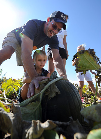 "Kerry Fritzler, left, and daughter, Spencer, 7,  pick out a green pumpkin for a witch carving.<br /> For more photos of pumpkin patches, go to  <a href=""http://www.dailycamera.com"">http://www.dailycamera.com</a><br /> Cliff Grassmick / October 2, 2011"