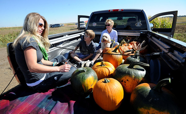 "Christa Story, left, her son, Cole, and mother, Pam Rasmussen, get in the back of the pick-up with their haul of pumpkins at Rock Creek Farms.<br /> For more photos and a video of pumpkin patches, go to  <a href=""http://www.dailycamera.com"">http://www.dailycamera.com</a><br /> Cliff Grassmick / October 2, 2011"