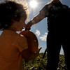 "Mallory Henry, 2, takes the pumpkin  from Amber Bryde at Rock Creek Pumpkin Farm on Thursday.<br /> For a video and more photos of pumpkin picking, go to  <a href=""http://www.dailycamera.com"">http://www.dailycamera.com</a>.<br /> Cliff Grassmick / October 6, 2011"
