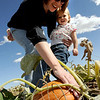 "Amanda Rogers helps Rachel Zimmerman, 1, pick out a pumpkin on Thursday at Rock Creek Farm, North of Broomfield.<br /> For a video and more photos of pumpkin picking, go to  <a href=""http://www.dailycamera.com"">http://www.dailycamera.com</a>.<br /> Cliff Grassmick / October 6, 2011"