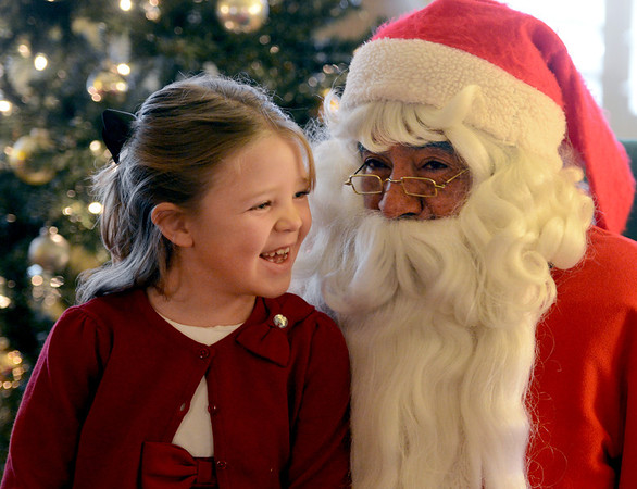 """Celeste Haverstick, 6, has some fun with Santa Claus ( Rich Lopez)  at Santa's House on Thursday. <br /> Santa's House features Santa and Mrs. Claus, musical performers, stories from Mother Goose, carnival games geared to the under 7 age group, and a craft/bake sale table for the entire family. Santa's House, a home decorated in a festive, traditional holiday style located at 890 11th Street in Boulder (Pi Beta Phi house), has been a Boulder tradition since 1972. This annual community event which takes place the first weekend in December is sponsored by the Boulder Area Alumnae Panhellenic.  Santa's House is open to the public from 10:00 AM - 4:00 PM December 1st and 2nd. Admission is $3 per person with proceeds donated to local children's charities.  For more information on Santa's House visit  <a href=""""http://www.SantasHouseBoulder.org"""">http://www.SantasHouseBoulder.org</a>. <br /> For more photos and a video, go to  <a href=""""http://www.dailycamera.com"""">http://www.dailycamera.com</a>.<br /> Cliff Grassmick  / November 29, 2012"""