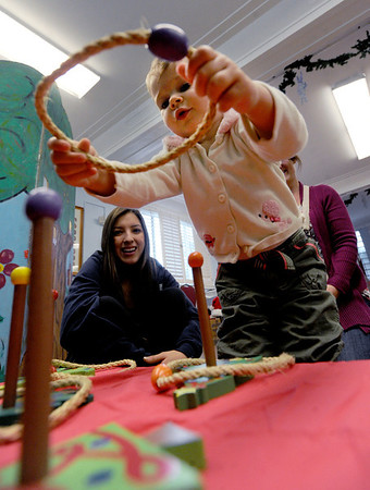 """Nela Prikrylova, 2, plays a ring toss game at Santa's House on Thursday.<br />  Santa's House features Santa and Mrs. Claus, musical performers, stories from Mother Goose, carnival games geared to the under 7 age group, and a craft/bake sale table for the entire family. Santa's House, a home decorated in a festive, traditional holiday style located at 890 11th Street in Boulder (Pi Beta Phi house), has been a Boulder tradition since 1972. This annual community event which takes place the first weekend in December is sponsored by the Boulder Area Alumnae Panhellenic.  Santa's House is open to the public from 10:00 AM - 4:00 PM December 1st and 2nd. Admission is $3 per person with proceeds donated to local children's charities.  For more information on Santa's House visit  <a href=""""http://www.SantasHouseBoulder.org"""">http://www.SantasHouseBoulder.org</a>. <br /> For more photos and a video, go to  <a href=""""http://www.dailycamera.com"""">http://www.dailycamera.com</a>.<br /> Cliff Grassmick  / November 29, 2012"""
