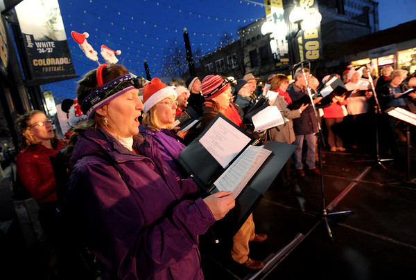 """Inger Barron, left, sings Christmas Carols with other members of the Boulder Chorale on Sunday.<br /> Santa Claus flipped  the switch that lit up the Pearl Street Mall and Boulder County Courthouse, as well as the star on Flagstaff Mountain.<br /> For a video and photo gallery  of the activities, go to  <a href=""""http://www.dailycamera.com"""">http://www.dailycamera.com</a>.<br /> Cliff Grassmick  / November 18, 2012"""