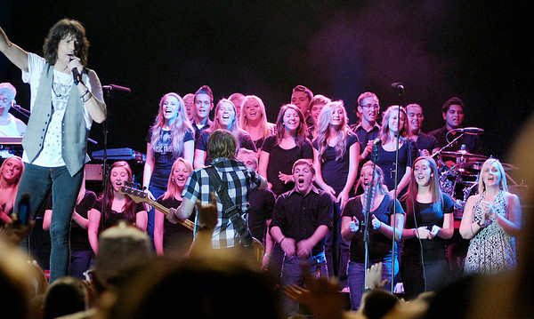 """The Anderson High School choir backs up Foreigner lead singer Kelly Hansen as they perform """"I Want to Know What Love Is"""" Saturday night at Hoosier Park."""