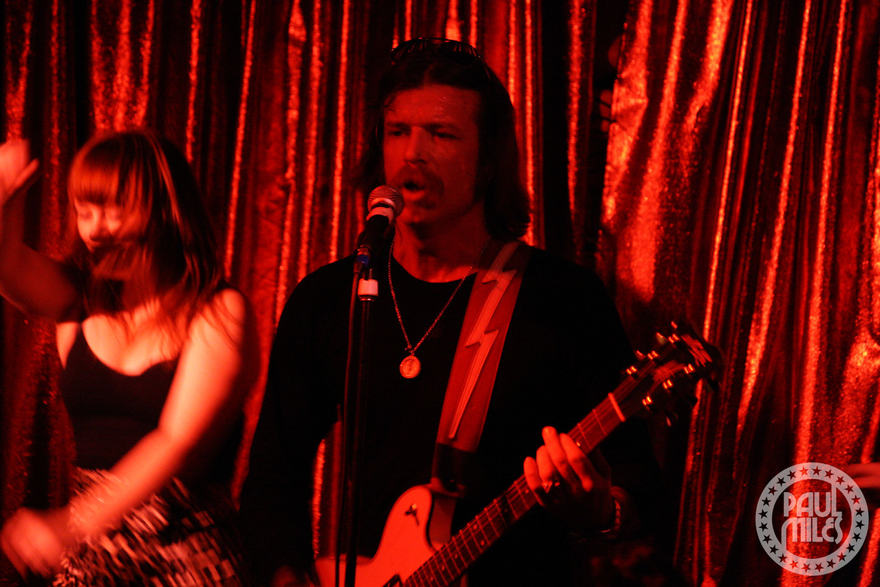 Jesse Hughes on stage at Cherry bar in Melbourne's ACDC Lane with Jamie McLean go-go dancing behind him.