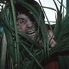 British heavy metal singer Ozzy Osbourne looks through plants at NYC hotel 1983