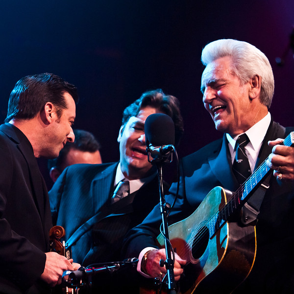 Jason Carter (fiddle), Ronnie McCoury (mandolin) and Del McCoury (guitar), singing in the traditional style around a single mic. © Sean Murphy
