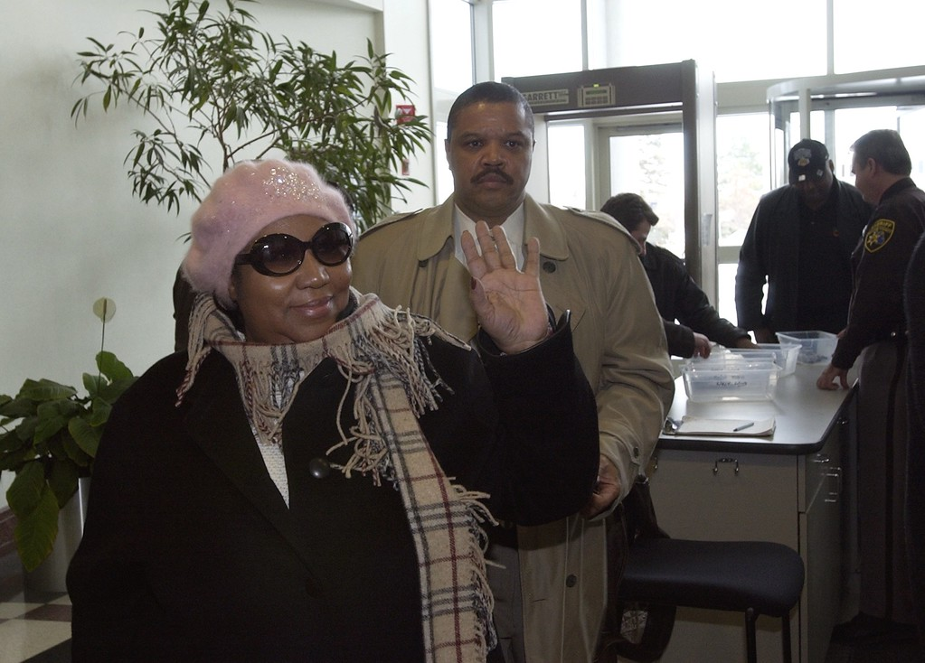 . Aretha Franklin arrives at the Oakland County Prosecutor\'s offices this afternoon responding to her investigative subpoena. Here, after passing through security, she waved to some of the onlookers standing in the hallway.