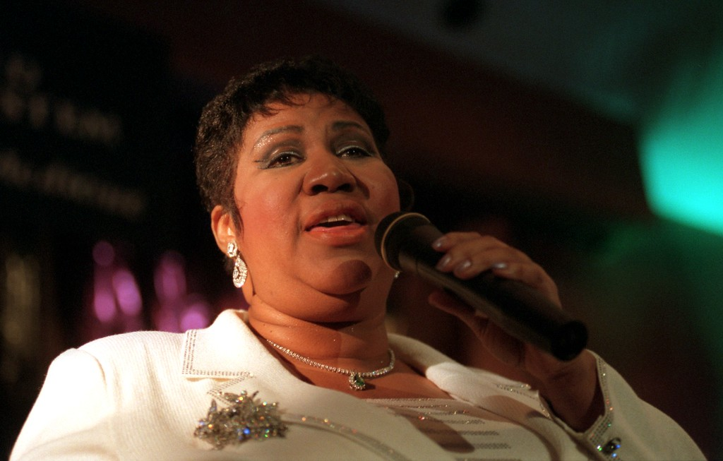 """. Motown legend Aretha Franklin sings Silent Night during a concert for patients at Henry Ford Hospital in Detroit yesterday afternoon. The half-hour show, that had the feel of a church revival, consisted mostly of gospel numbers. Looking around at the room full of people, many of whow were in wheelchairs , with Ivs in town, Franklin said, \""""For the next twenty minutes or so, No body in here is going to be sick.\"""""""