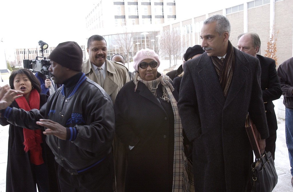 . Aretha Franklin (center, pink hat) arrives at the Oakland County Prosecutor\'s offices this afternoon responding to her investigative subpoena.