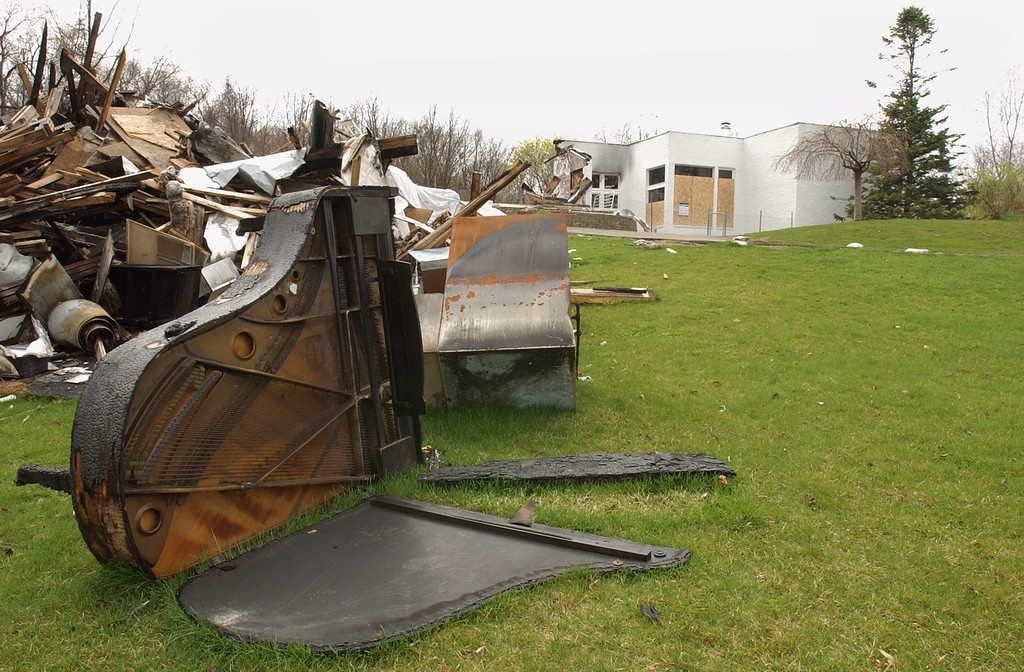. Debris left over from a house fire, including a burnt piano, is still left on the lawn next to a boarded-up home in Bloomfield Township, Mich., Wednesday, April 30 2003, owned by singer Aretha Franklin.