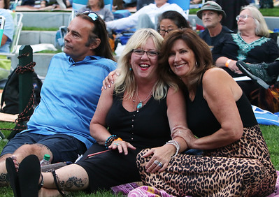 The Eagles Hotel California, a tribute band, plays at Boarding House Park in the first concert of the 2021 Lowell Summer Music Series. From left, Bobby DiMichele, his girlfriend Debbie McCann, and her friend Diane Nolet, all of Lowell. SUN/Julia Malakie