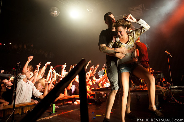 A fan continues dancing as she is escorted off the stage after body surfing while Matt & Kim perform at their sold-out show on October 15, 2010 at State Theatre in St. Petersburg, Florida