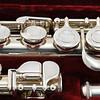 Close-up of silver concert flute in velvet-lined case, showing details of keys, pads and mechanism